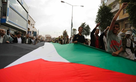 People hold a giant Palestinian flag as they demonstrate to denounce Israeli air strikes on the Gaza strip, in Sanaa July 10, 2014 (The Guardian).