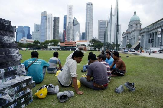 A migrant construction worker throws his boots to the side as he takes a break with fellow workers at the end of his shift in the central business district in Singapore